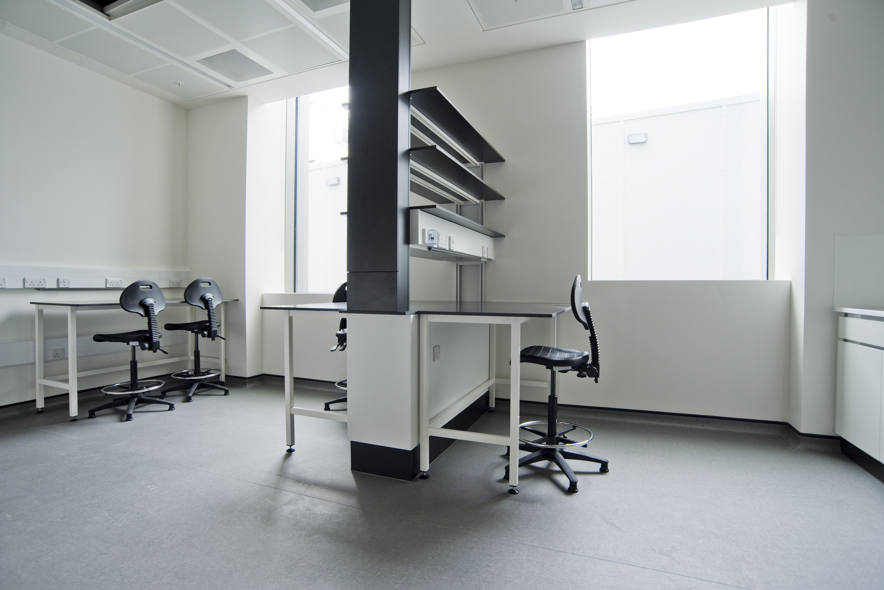 This image shows one of the larger proprietary labs in the Bioescalator. The room has 2 large windows on the back wall. There are 2 desks with chairs in the middle of the room. There is shelving above those desks. There is also another desk with chairs to the left of the room. There is a bench top to the right of the room.