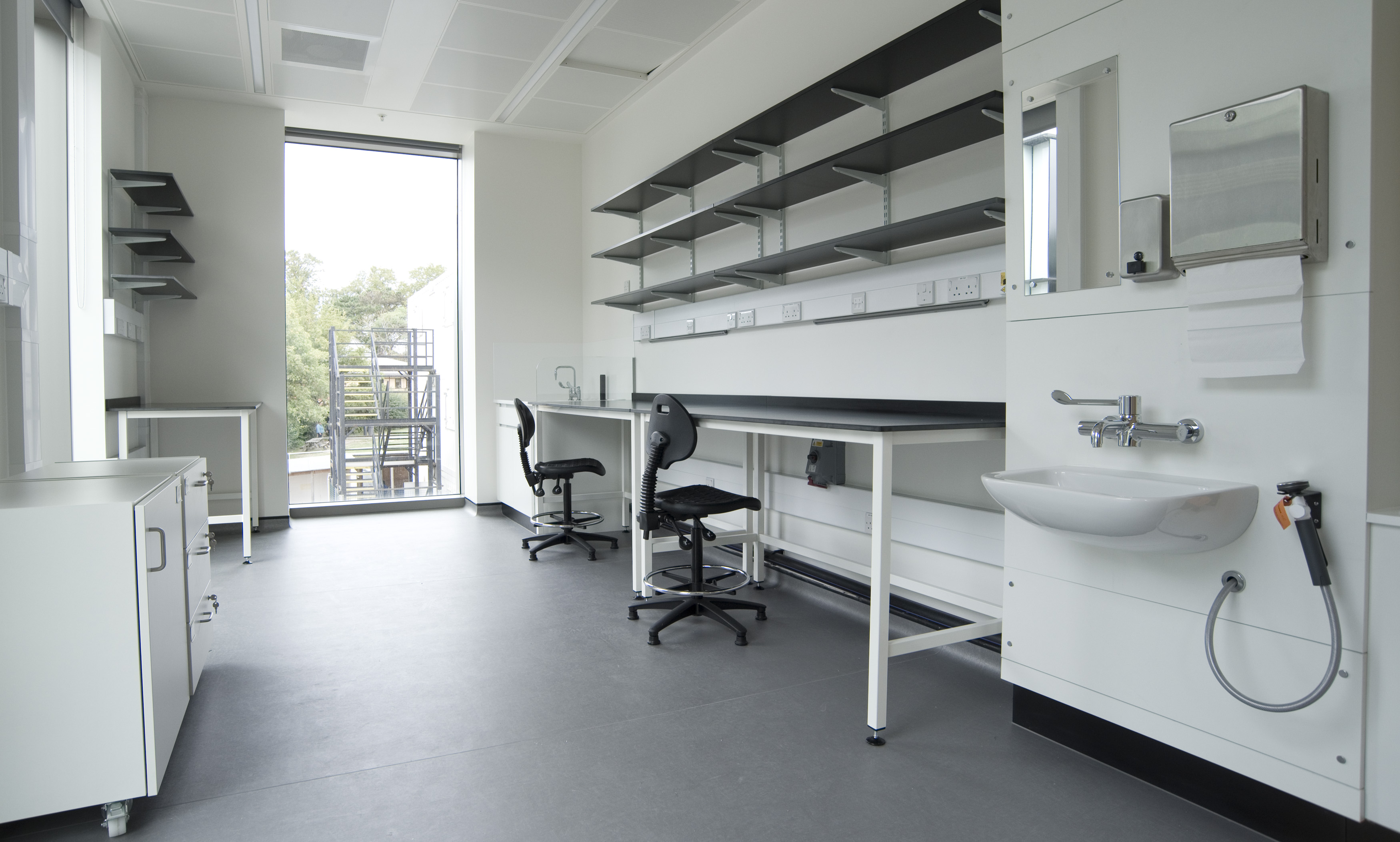 This image shows one of the smaller BioEscalator proprietary lab spaces. The room has a large window at the back. There are 3 large desks with desk chairs, 2 on the right and one on the left. There is shelving on both walls above the desks. There is also a cupboard on the left and a sink on the right wall towards the front of the room.
